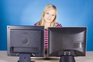 A girl using a computer with two monitors.
