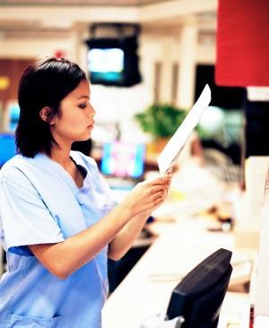 A nurse reading a chart.