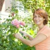 A woman smiling while gardening.