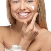 Woman putting on eye cream.