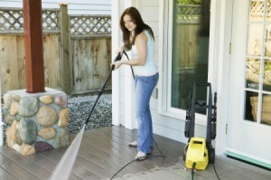 Woman Spring Cleaning Outside With Pressure Washer