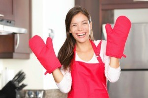 Woman wearing oven mitts.