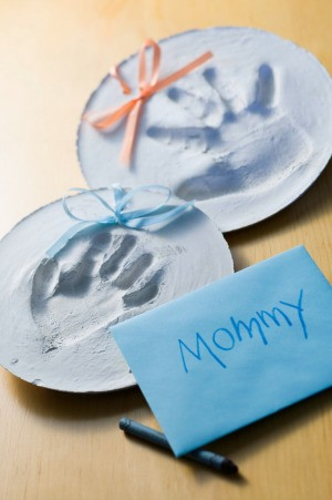 Two child's hand print ornaments.