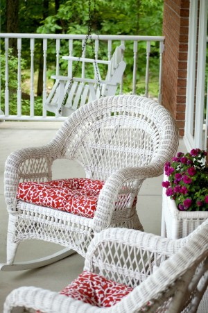 Outdoor wicker style chairs with fabric covered seat cushions.