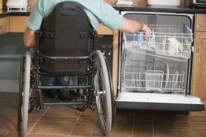 Man in Wheelchair Washing Dishes