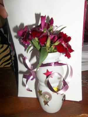 A mini flower vase made from a recycled container.
