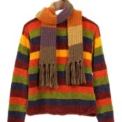 Colorful sweater hanging in a closet.