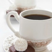 Coffee being served at a wedding in a white cup with a chocolate candy.