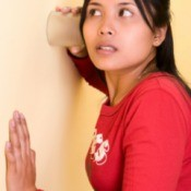 A woman putting a class up to a wall to listen.