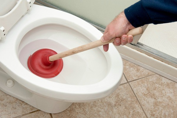 unclogging toilet using plunger