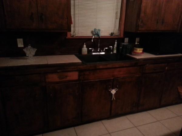 Dark brown cabinets in dated kitchen.
