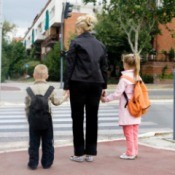 A mom and two kids crossing the street.