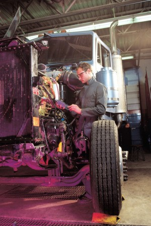 man servicing a semi truck