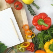 Writing a cookbook, in the kitchen. Photo of a notepad surrounded by vegetables.