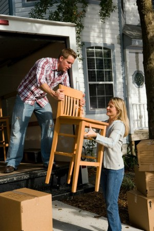 A husband and wife unloading furniture from a moving van.