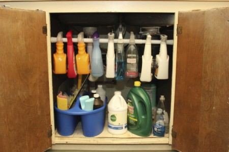Spray bottles hanging on bar under sink.