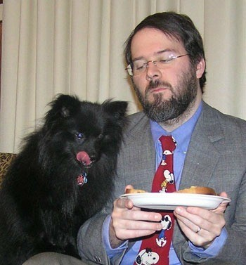 Black Pomeranian looking at man's food while licking her lips.