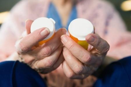 Old woman holding prescription drug bottles.