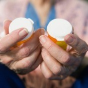 Old woman holding prescription drug bottles.