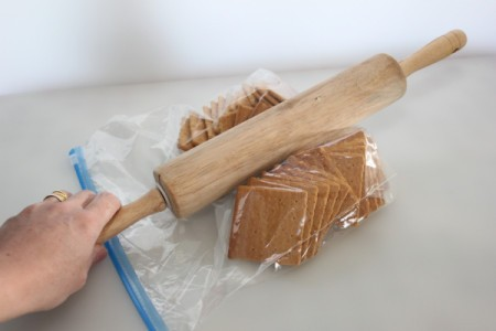 Crushing crackers in a plastic bag with rolling pin.