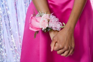 A sweet pink corsage worn by a girl in a pink dress.