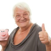 An older woman holding a piggy bank and giving a thumbs up.