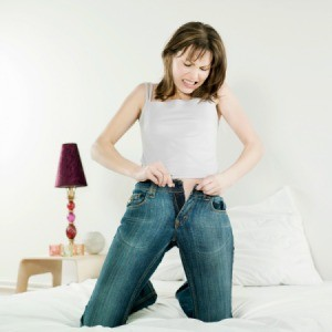 A woman struggling to put jeans on.