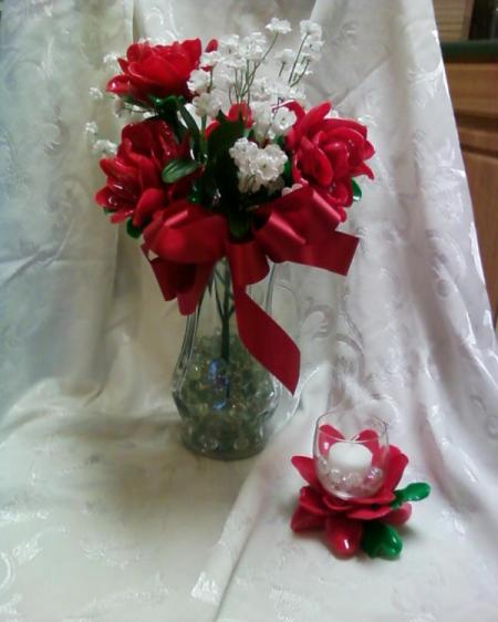 Vase with red spoon flowers mixed with white artificial flowers. Votive holder in foreground.