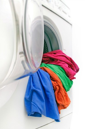 Colorful clothing hanging out of a washing machine.
