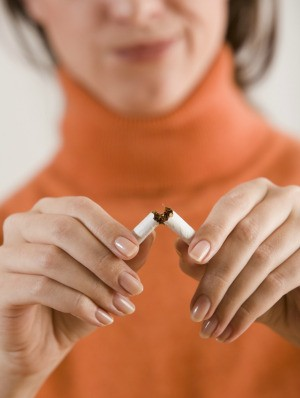 A woman breaking a cigarette in half.