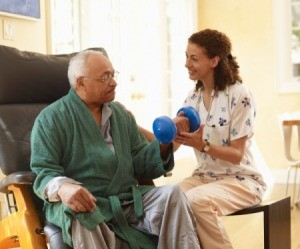 An older man working with a trainer at home.