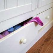 A chest of drawers with clothing in them.