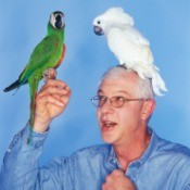 Birds perched on a man's hand and shoulder.