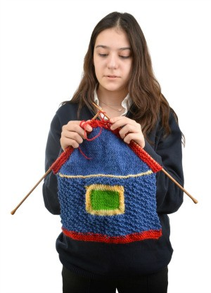 A teen knitting a house.
