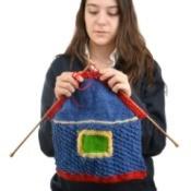 A teen knitting a house.