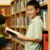 Photo of a sixth grading reading a book in a library.