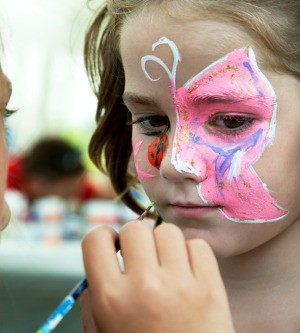A girl having her face painted.