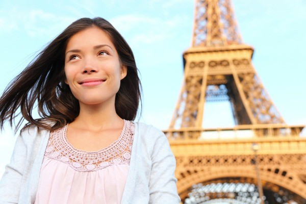 health insurance when living abroad thriftyfuna woman living in paris standing in front of the eiffel tower