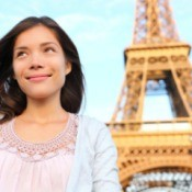 A woman living in Paris standing in front of the Eiffel Tower.