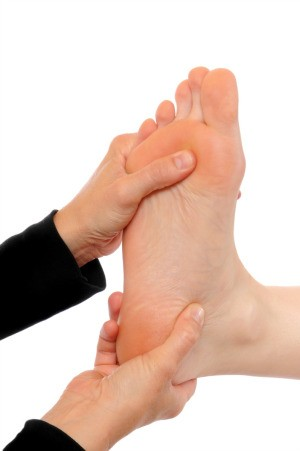 Using acupressure on a foot.