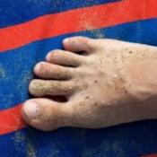 Sandy feet on a towel at the beach.