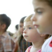 Children watching a show at a park.