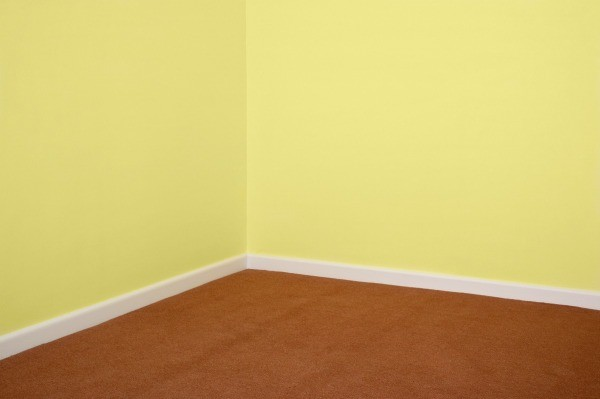 a room with wall to wall carpet that is buckling