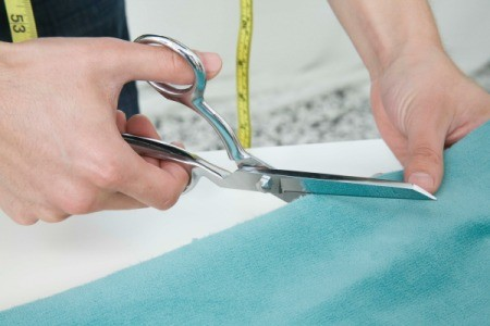 Someone cutting light blue fabric with scissors.
