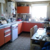 Kitchen with orange cupboards.
