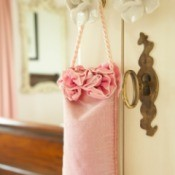 A pink bag filled with potpourri hanging from a door handle.