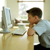 A boy using a computer in the living room.