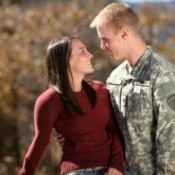 Girl standing with her soldier boyfriend.