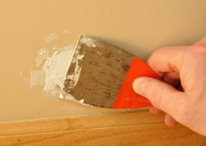 Applying putty to a damaged portion of a painted wall.