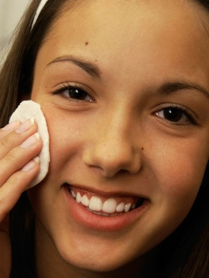 A girl looking in the mirror and using a medicated pad to treat acne.
